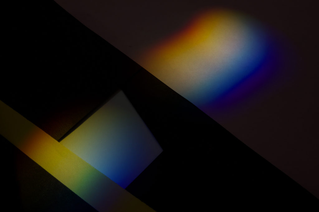 Dark and moody photograph of color spectrum cast on architectural details.