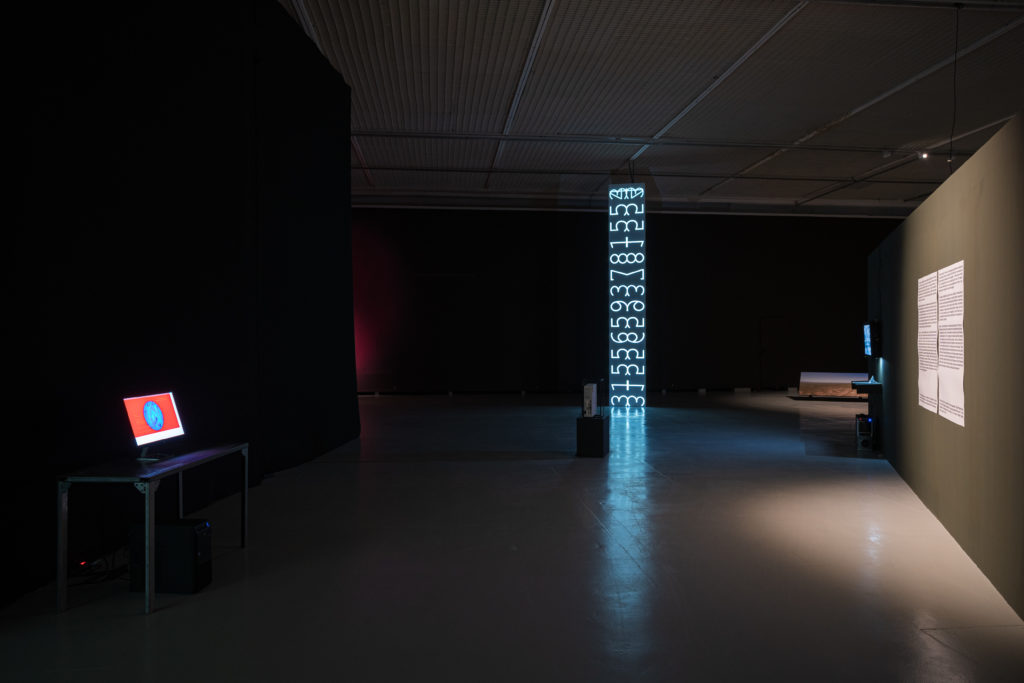 An art installation with a screen on the left with a red and blue image. In the center a column of numbers in LED.